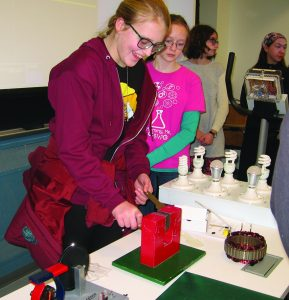 Girls passing copper bar through horseshoe magnet
